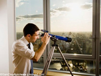 Picture of a man looking through a telescope at a city from high up in a high rise office. The young adult businessman is wearing a white dress shirt and tie. He has his hand on the eyepiece and is observing the city through the lens.